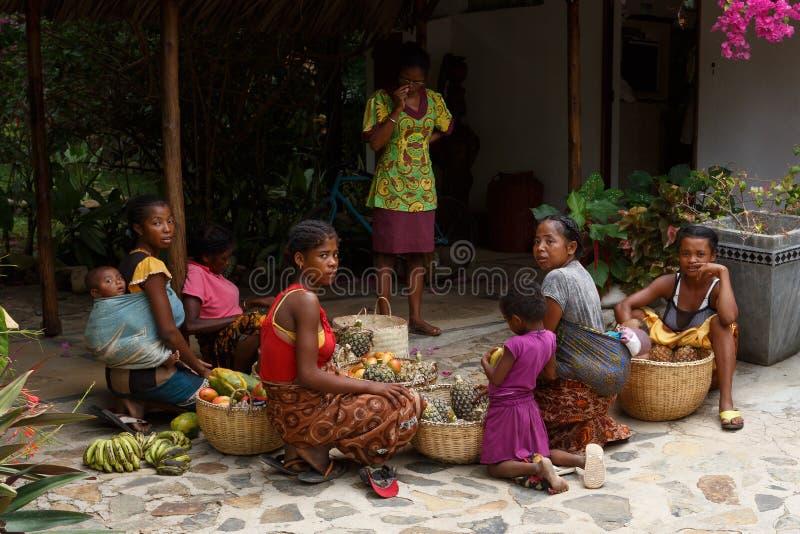 Madagassische Frauen, die Korb der Frucht für Straßenmarkt Verkauf vorbereiten, stockbild