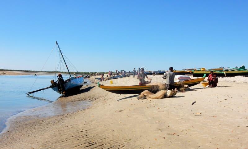 Madagassiska kanoter på stranden med funktionsdugliga fiskare royaltyfri bild