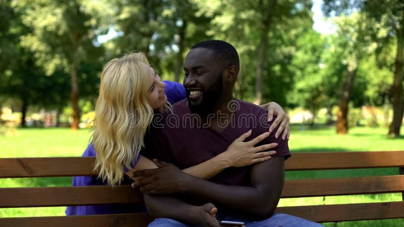 Madame étreignant l'homme d'afro-américain par derrière, riant et souriant, surprise image libre de droits