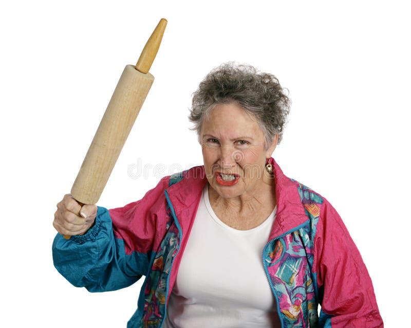 Madame aînée fâchée avec le roulement photos stock