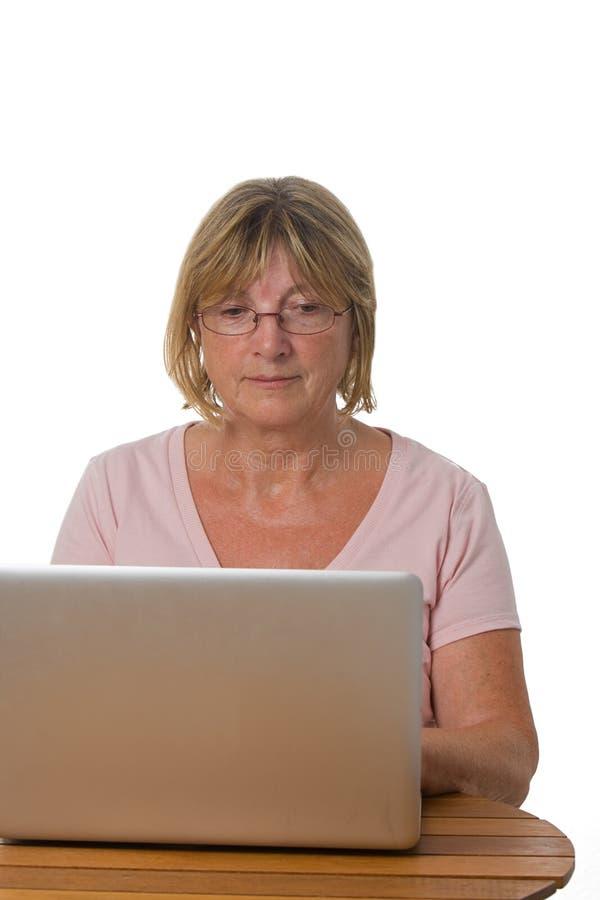 Madame aînée Using Laptop photo stock