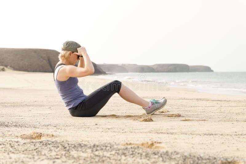 Madame active Doing Sit-Ups par le bord de la mer photos libres de droits