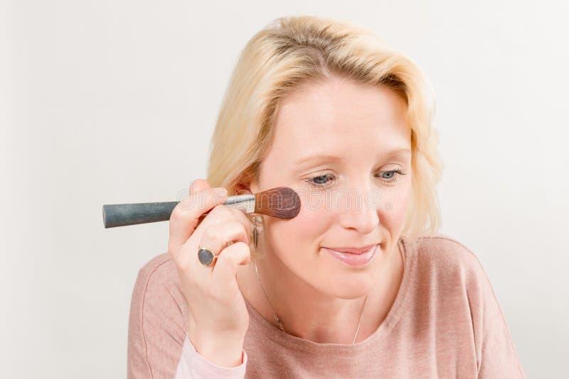 Madame Applying Blush avec une brosse photographie stock
