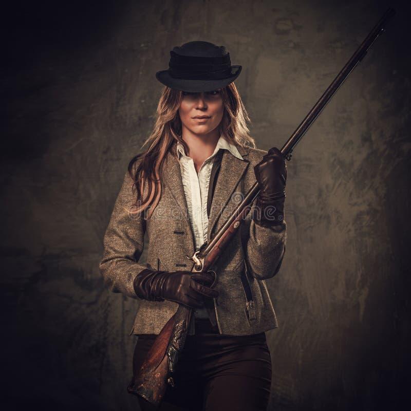 Madame avec le fusil de chasse et le chapeau de l'ouest sauvage sur le fond foncé photo stock