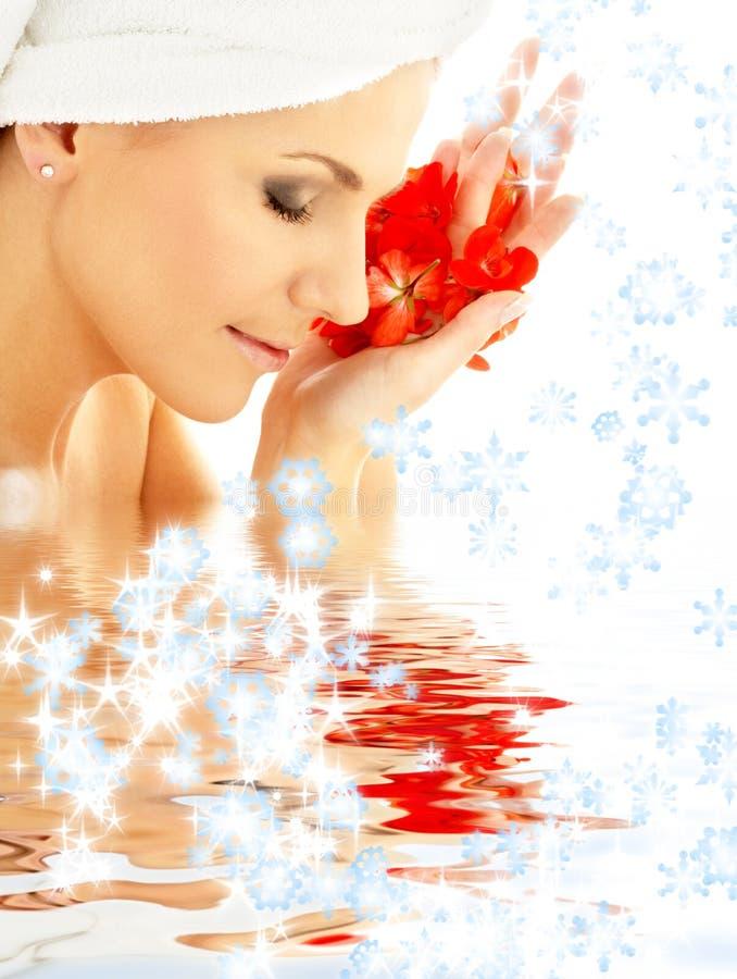 Madame avec les pétales et les flocons de neige rouges dans l'eau image stock