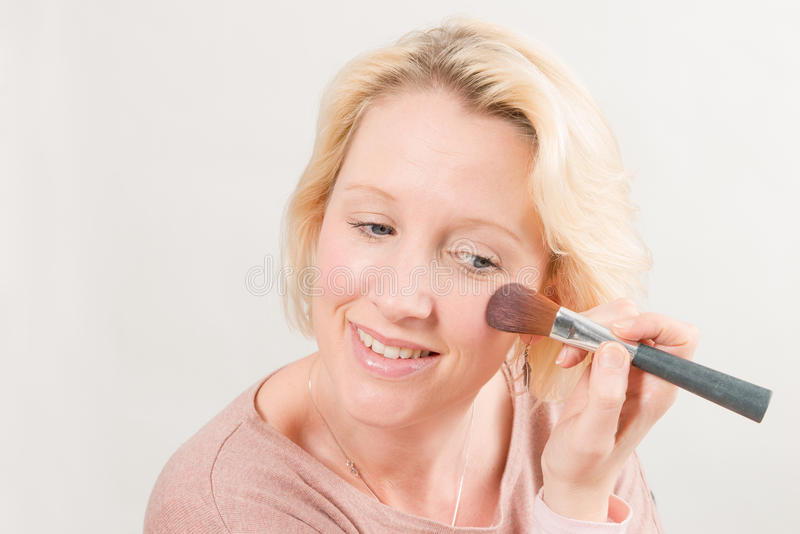 Madame blonde Smiling et maquillage d'application photo stock