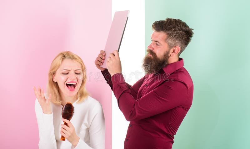 Madame chantent employant la brosse de cheveux comme microphone tandis que l'homme ennuyait aller battait son ordinateur portable image libre de droits