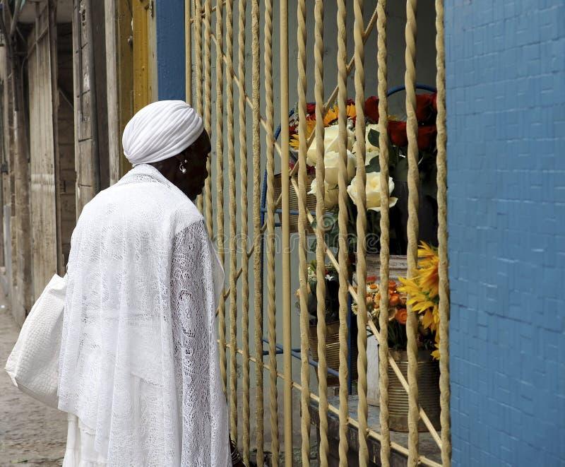 Madame cubaine Dressed In White regardant des fleurs image stock