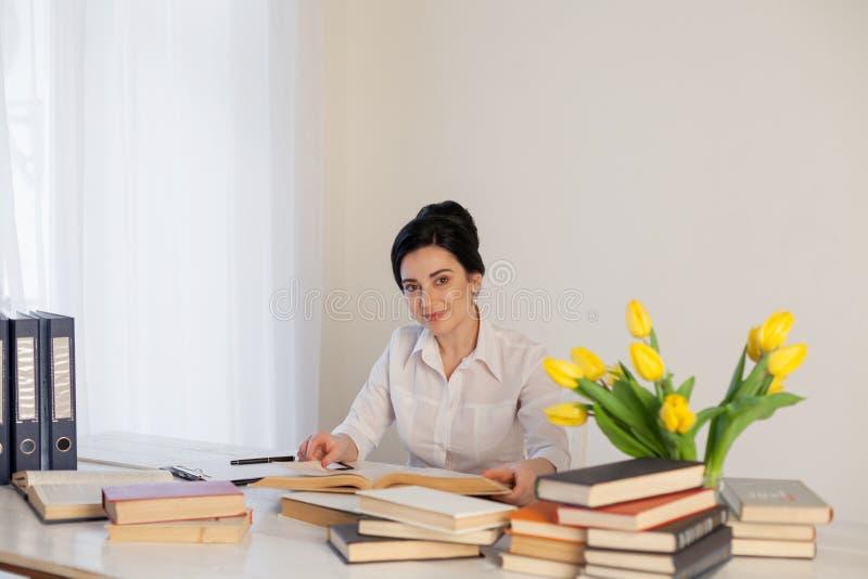 Madame d'affaires de professeur lit des livres dans le bureau photos stock