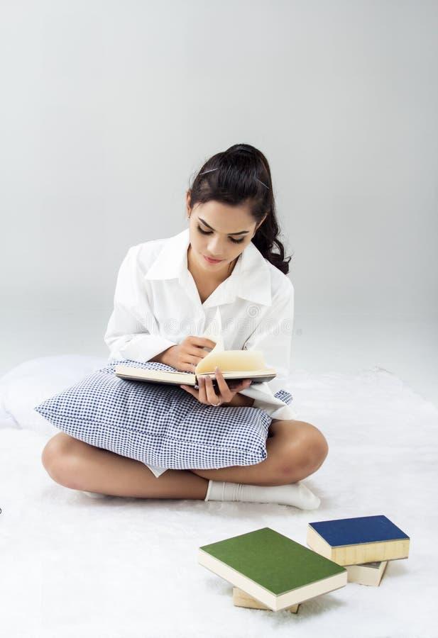 Madame dans la chemise blanche s'assied sur le lit photographie stock