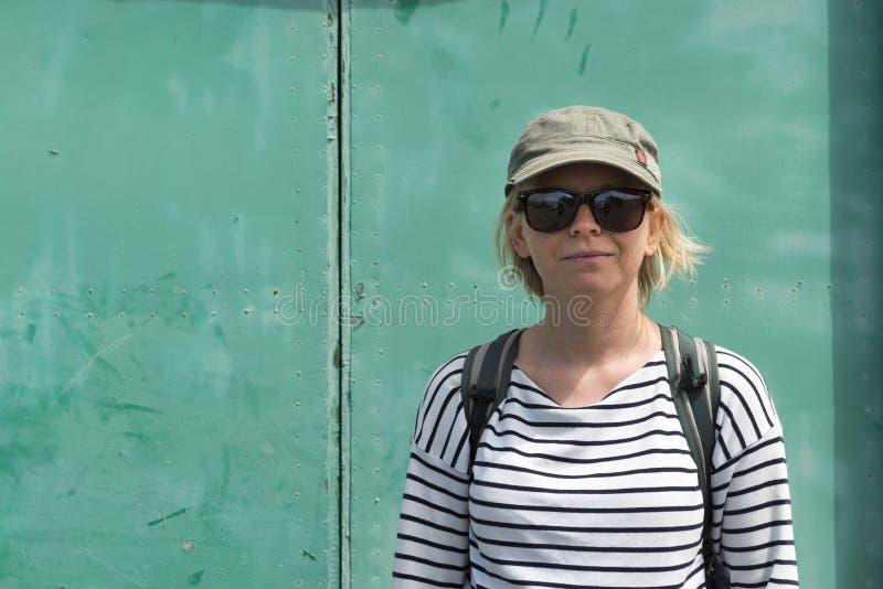 Madame dans la chemise rayée, les lunettes de soleil, et le chapeau avec un sac à dos photographie stock