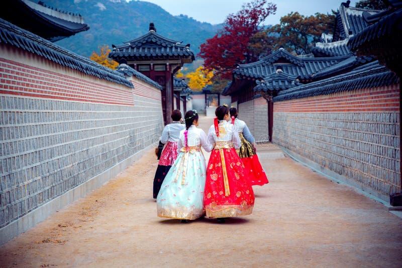 Madame dans la promenade de robe de hanbok dans le palais de Séoul dans le jardin d'automne de ginkgo images stock