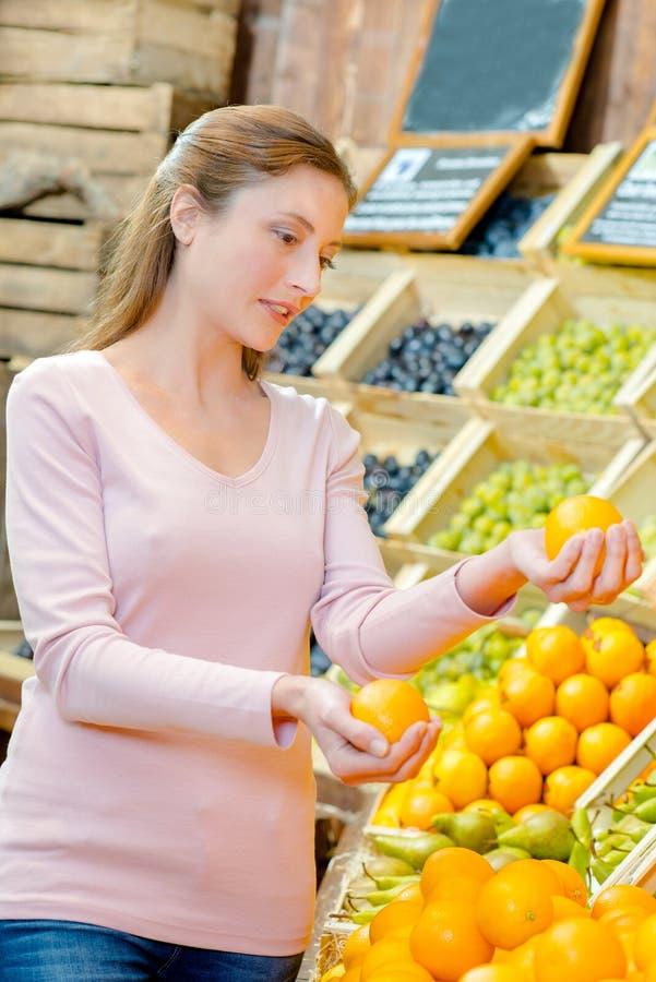 Madame dans les marchands de légumes jugeant oranges dans chaque main photo stock