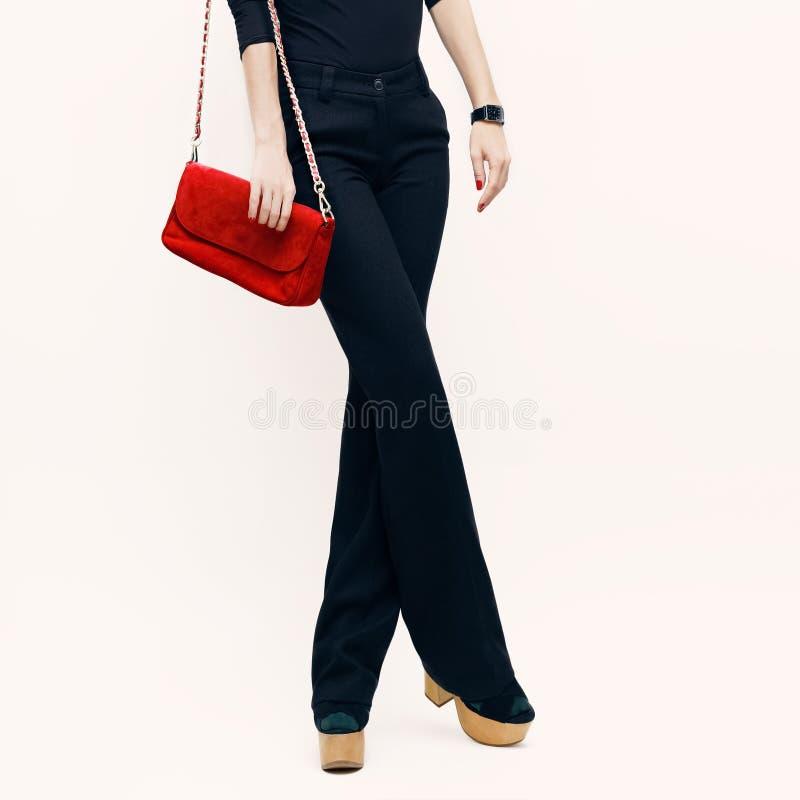 Madame dans les pantalons noirs classiques et le chemisier noir avec un clutc rouge image stock