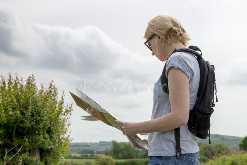 Madame Hiker Holding et lecture d'une carte en Sunny Outdoors images stock