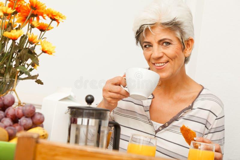 Madame mûre heureuse Having Breakfast image stock