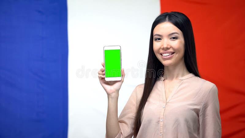 Madame montrant le smartphone avec l'écran vert, drapeau français sur le fond, appli de voyage photographie stock