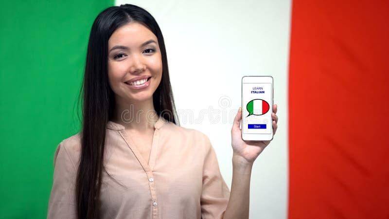 Madame montrant le téléphone portable avec pour apprendre l'appli italien, drapeau sur le fond, éducation images stock