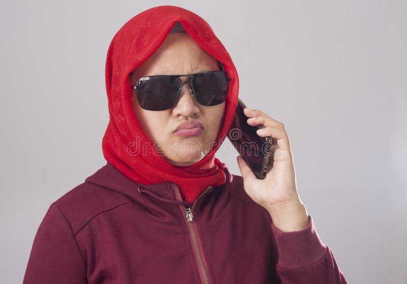 Madame musulmane dans le service de mini-messages parlant rouge au téléphone, expression fâchée de Disapponted de renversement image stock