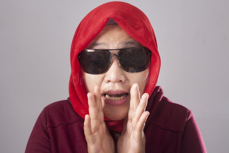 Madame musulmane en rouge chuchotant quelque chose image stock