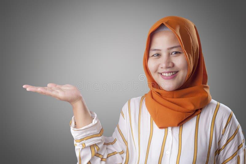 Madame musulmane Presenting Something de son côté avec l'espace de copie photo stock