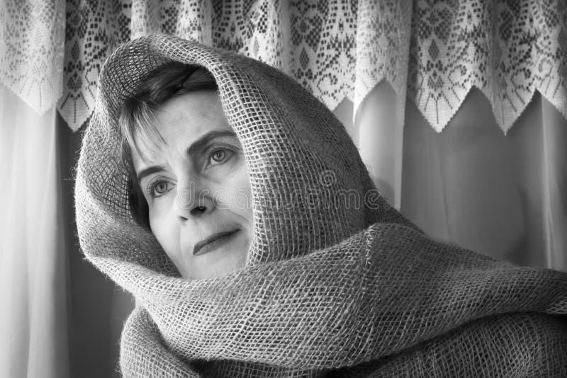 Madame portant une bâche principale de toile de jute regardant hors d'une fenêtre photos libres de droits