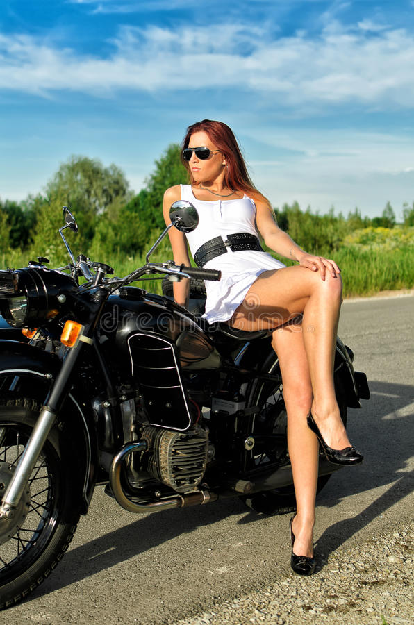 Madame posant sur la moto image stock