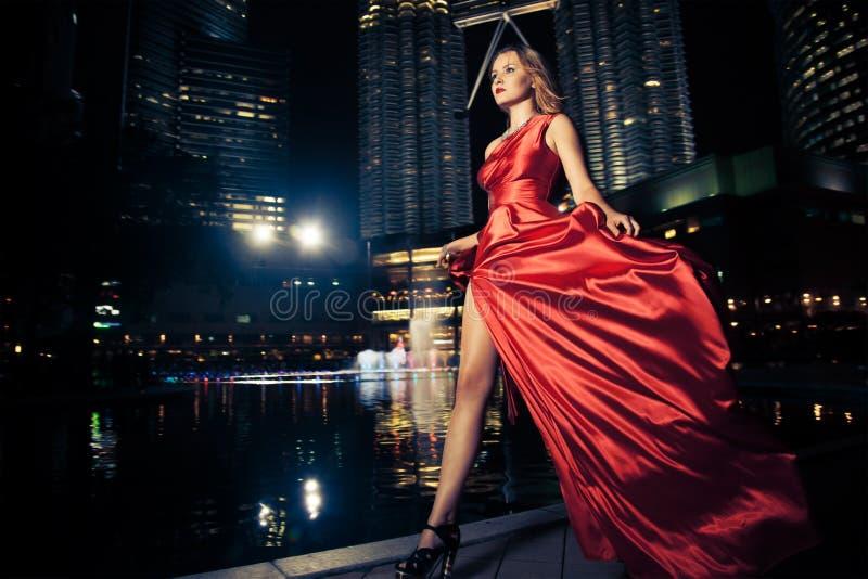 Madame In Red Dress de mode et lumières de ville images stock