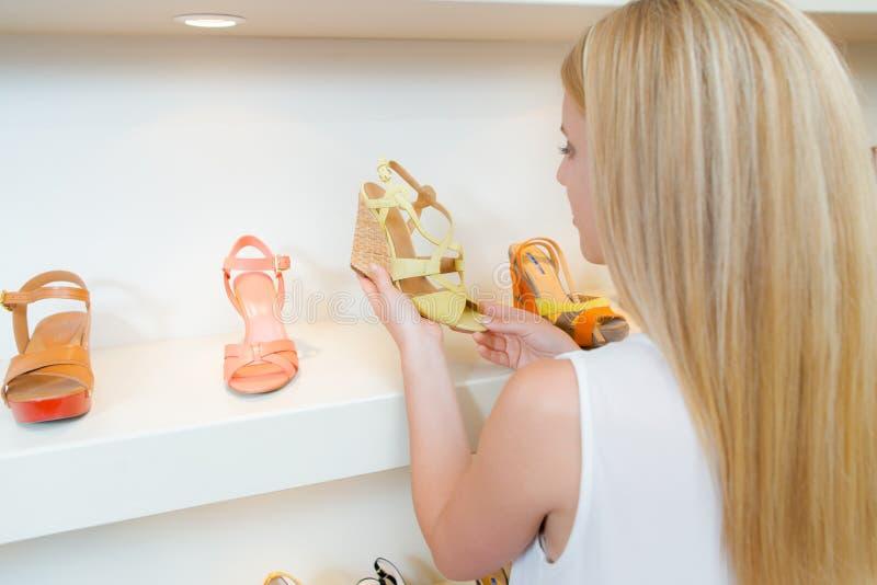 Madame regardant des sandales dans la boutique de chaussure image libre de droits
