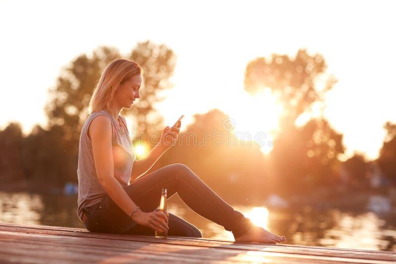 Madame s'asseyant sur le dock près de l'eau au coucher du soleil photo stock