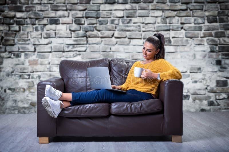 Madame s'asseyant sur un sofa détendant et à l'aide d'un carnet photo stock