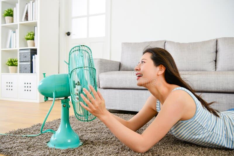 Madame se couchant sur le plancher et à l'aide du ventilateur électrique photographie stock