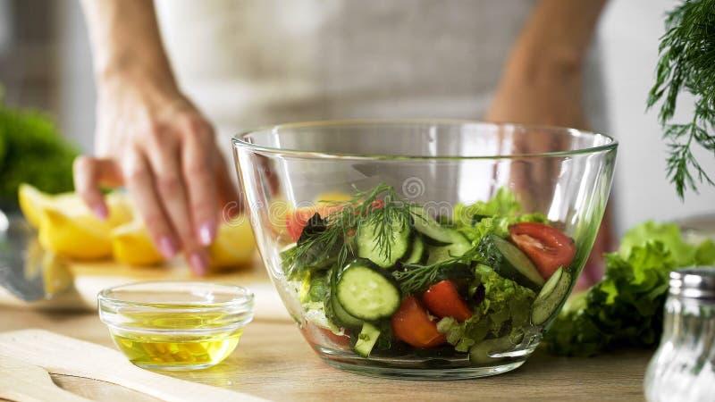 Madame tenant le morceau de citron et l'huile d'olive pour s'habiller, saladier organique sur la table photographie stock