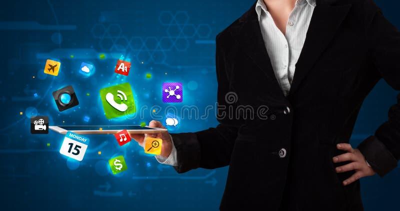 Madame tenant un comprimé avec les apps et les icônes colorés modernes photo libre de droits
