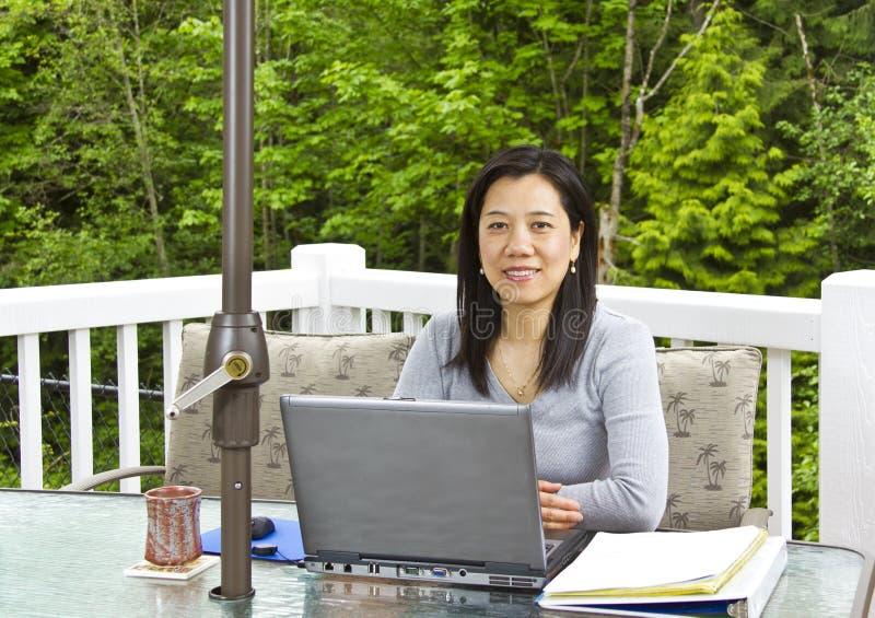 Madame travaillant à la maison sur le patio extérieur photos libres de droits