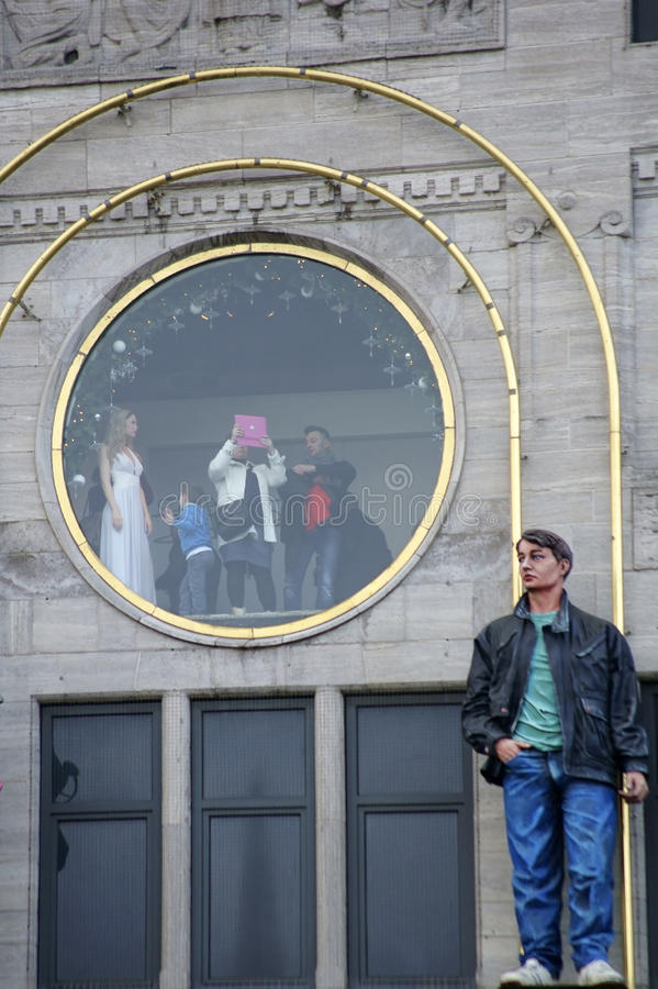 Madame Tussaud Amsterdam. Amsterdam, The Netherlands - December 29, 2014: Tourists photographing with a Tablet PC from a round picture window of the wax museum stock photography