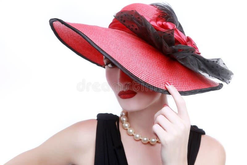 Madame Wearing Red Hat sur le fond blanc image libre de droits