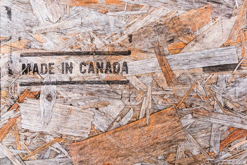 Made in Canada text on recycled wood board. Background. Recycled compressed wood chippings board background. Texture of recycled wooden material background royalty free stock images