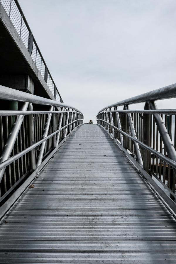 Abstract view of a woman sitting at a bench at the top of a metal harbour walkway. Made completely from metal, this non slip walking is seen at an New England stock image