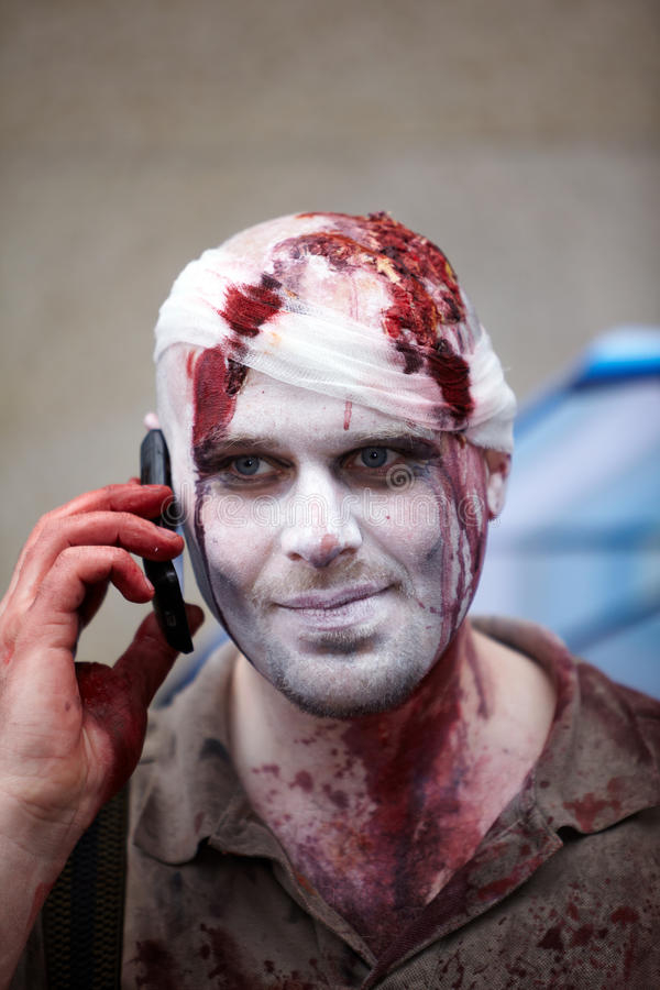 Made-up participant with bandage at Zombie Parade. MOSCOW - MAY 14: Unidentified made-up participant with a bandaged bloody head keeps cell phone at his ear at stock images