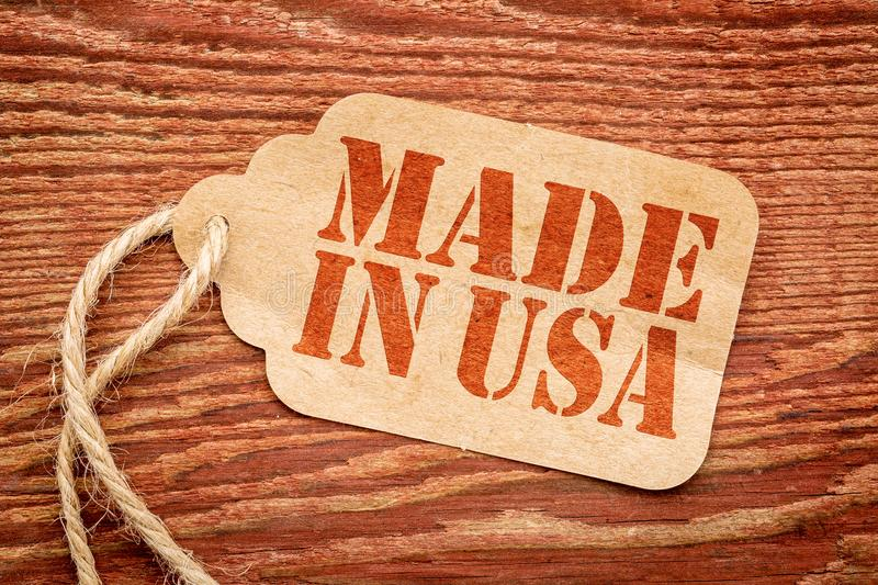 Made in USA - price tag. Made in USA sign - red stencil text on a paper price tag against grunge wood stock image