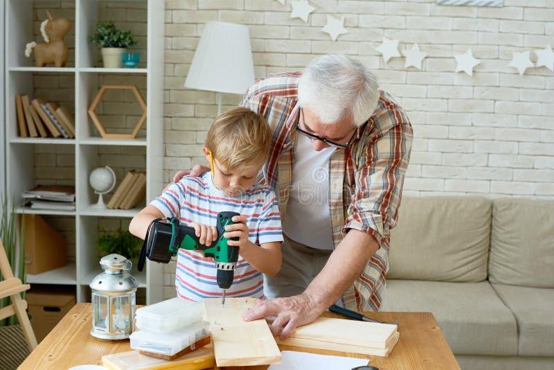 Madeira bonito da perfuração de Little Boy com ajuda do vovô foto de stock royalty free