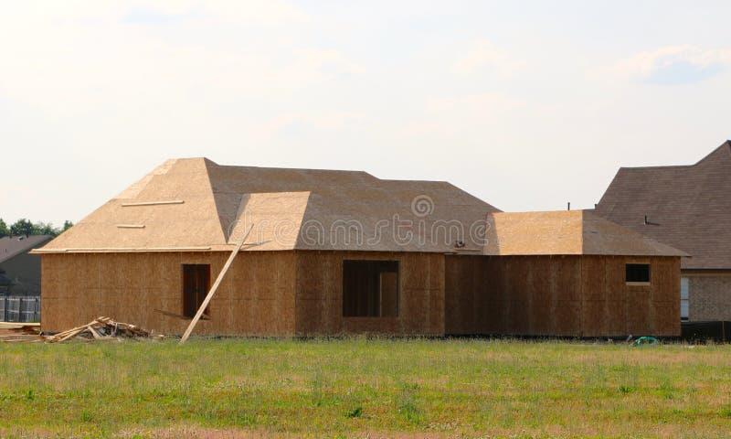 A madeira cobriu o quadro de uma casa suburbana sob a construção fotos de stock