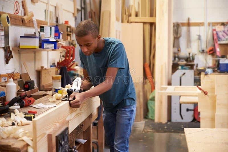 Madeira de aplanamento do aprendiz na oficina da carpintaria foto de stock royalty free