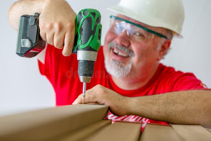 Madeira de montagem do trabalhador alegre com broca-movimentação fotografia de stock
