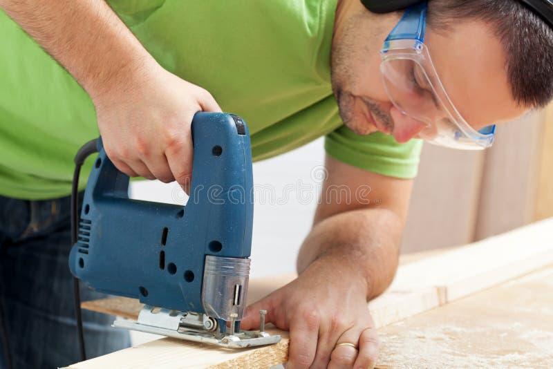 Madeira de trabalho do homem com serra elétrica fotografia de stock