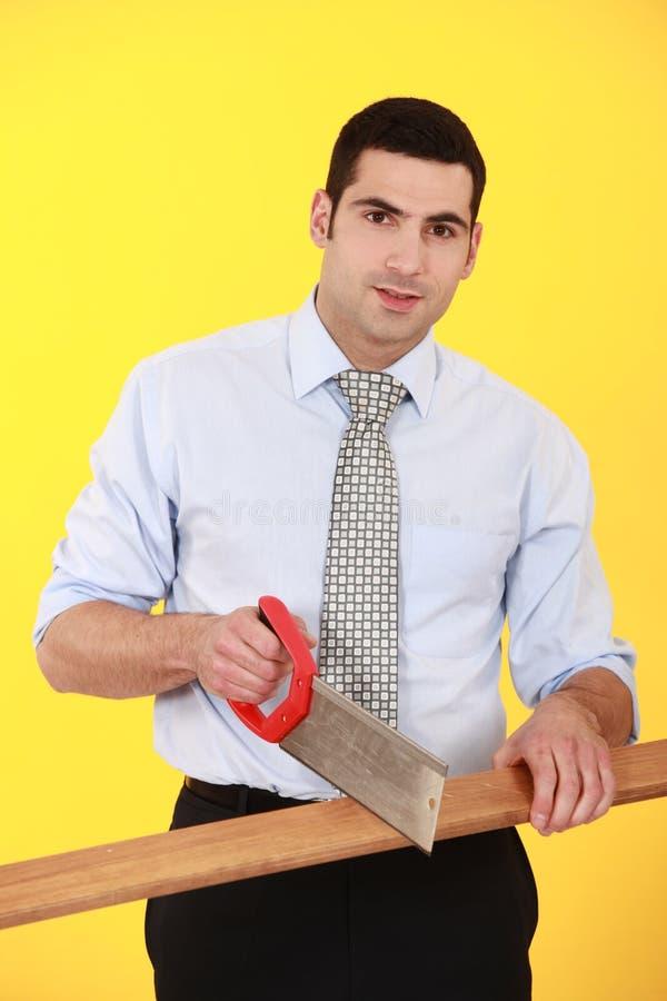 Madeira do sawing do homem de negócios foto de stock