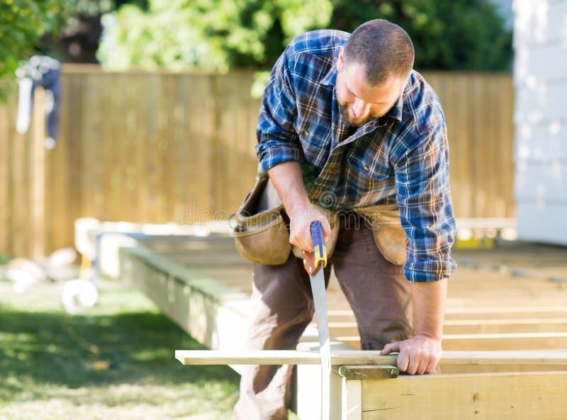 Madeira do sawing do trabalhador no canteiro de obras imagens de stock