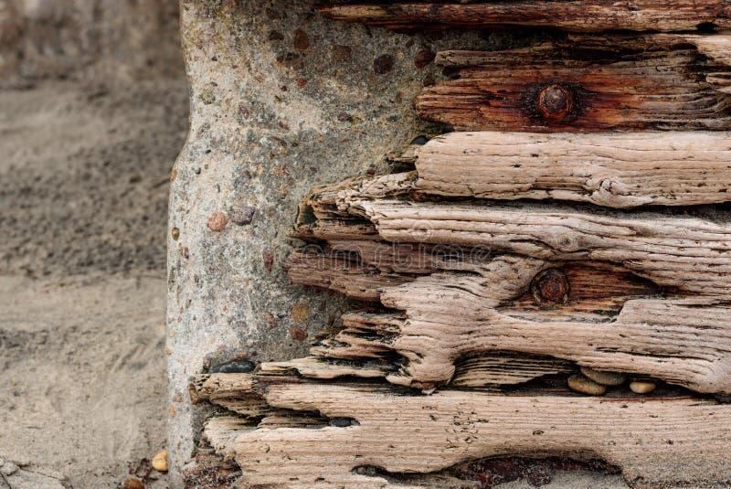 A madeira lançada à costa com parafusos oxidados ajustou-se contra uma parede de pedra concreta, fundo do grunge do vintage fotos de stock