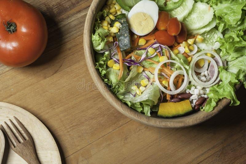 Madeira saudável da bacia de salada, placas de madeira e cutelaria no assoalho de madeira imagens de stock royalty free